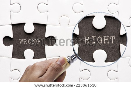 "Magnifying glass searching missing puzzle peaces ""wrong and right""  - stock photo"