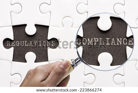 """Magnifying glass searching missing puzzle """"regulation and compliance""""  - stock photo"""