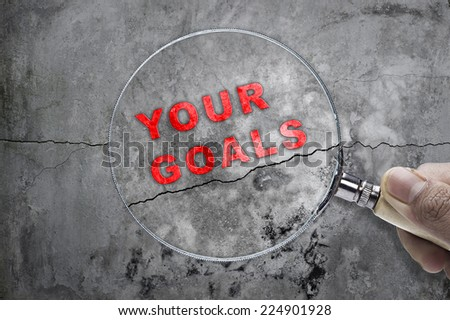 "Magnifying glass searching ""YOUR GOALS"" over cracked wall as a background - stock photo"