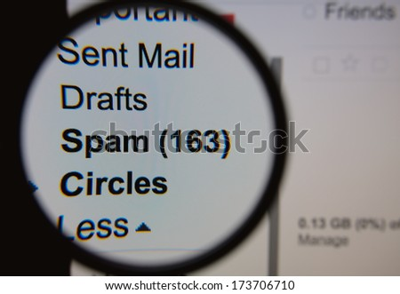 Magnifying glass showing a spam folder in the mailbox on the monitor screen. - stock photo