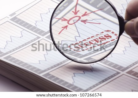 Magnifying glass showing the success on business and stock market. - stock photo