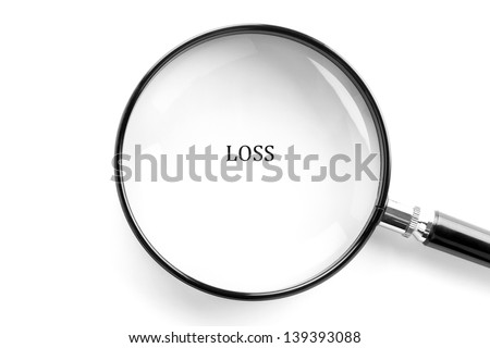 Magnifying glass showing the word loss on white paper