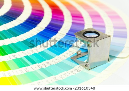Magnifying glass standing on color guide on a white background - stock photo