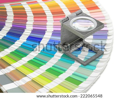 Magnifying glass standing on swatches palette on a white background - stock photo