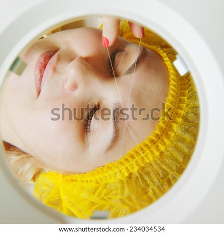 Magnifying glass view to threading facial hair removal procedure - stock photo