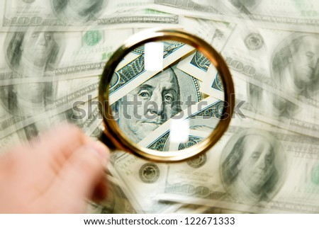 magnifying glass with background of dollars