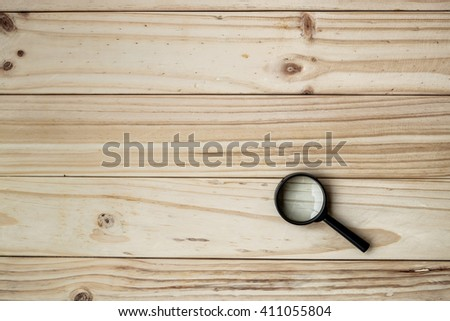 Magnifying Glass with Black Handle on the wooden background - stock photo