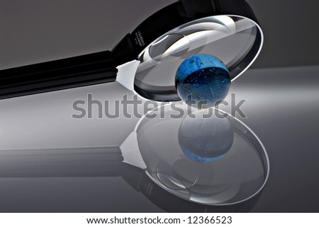 Magnifying glass with marble on a reflective surface - stock photo