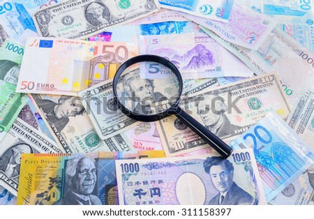 Magnifying glass with the international bank note
