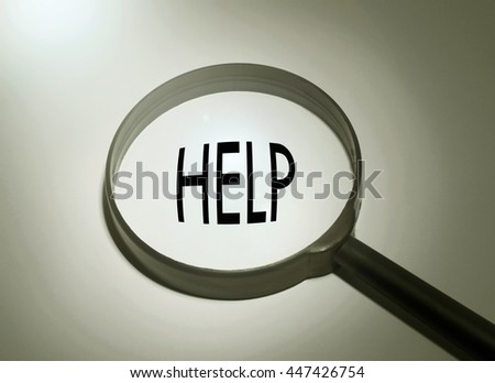 Magnifying glass with the word help. selective focus - stock photo