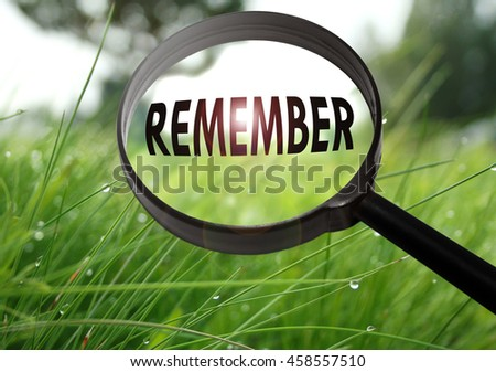 Magnifying glass with the word remember on grass background. Selective focus - stock photo