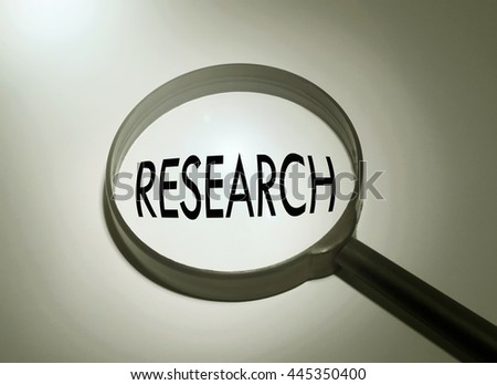 Magnifying glass with the word research. Searching research - stock photo