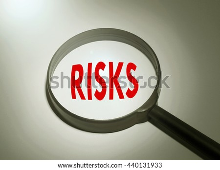 Magnifying glass with the word risks. Searching risks