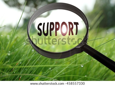 Magnifying glass with the word support on grass background. Selective focus - stock photo