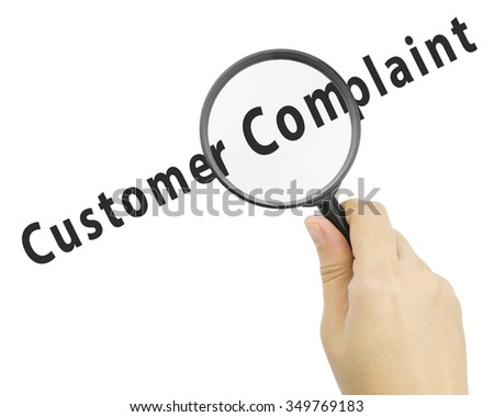 Magnifying glass with word CUSTOMER COMPLAINT in hand