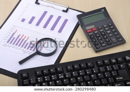 """Magnifying Glass With Yearly Graph Bar Representing """"Sales/Expenses"""" with Calculator and Keyboard, Selective Focus  - stock photo"""