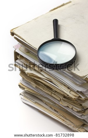 Magnifying lens  on the stack of old files - stock photo