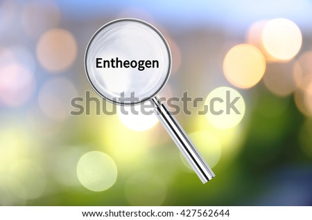 Magnifying lens over background with text Entheogen, with the blurred lights visible in the background. 3D rendering. - stock photo