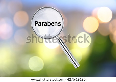 Magnifying lens over background with text Parabens, with the blurred lights visible in the background. 3D rendering. - stock photo