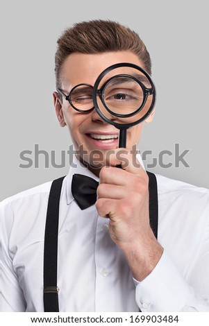 Magnifying you. Portrait of cheerful young man in bow tie and suspenders holding magnifying glass in front of his eye and smiling