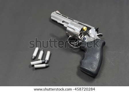 Magnum gun with gold bullets , Magnum revolver and one bullet, Magnum on black paper, Russian roulette game , Dead or Alive. - stock photo