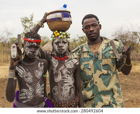 MAGO NATIONAL PARK, OMO VALLEY, ETHIOPIA - JANUARY 01, 2014: Unidentified boys from Mursi tribe and Ethiopian solder with machine guns in Mirobey village. - stock photo