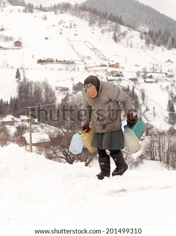 MAGURA, ROMANIA - JANUARY 26: Old woman carries empty bottles in Magura on January 26, 2013. The mountain village Magura is located at an 1000 meters altitude, in the Piatra Craiului national park.  - stock photo