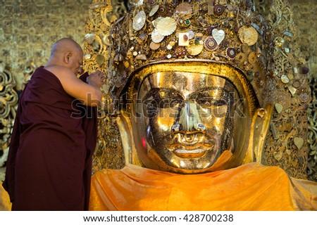 MAHAMUNI BUDDHA TEMPLE, MANDALAY, MYANMAR - DEC 26: Unidentified monk make traditional ceremony by wash Mahamuni Buddha face on December 26,2015 in Mahamuni Buddha Temple, Mandalay, Myanmar. - stock photo
