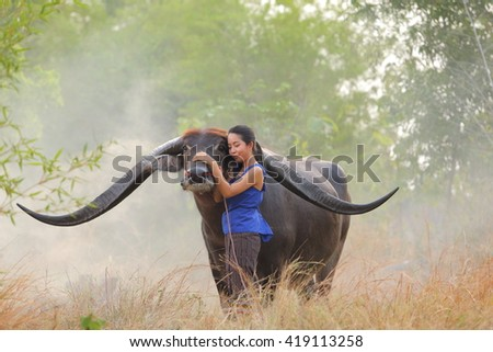 MAHASARAKHAM, THAILAND - MAY 8, 2016: Culture of coexistence of the woman and Buffalo, Mahasarakham, Thailand.