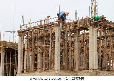 MAHASARAKHAM, THAILAND - MAY 22 : Unidentified workers are working on city hall building site on May 22, 2013 in Mahasarakham, Thailand.