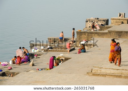 Maheshwar, India - 3 February 2015: People washing clothes on sacred river Narmada ghats. To Hindus Narmada is one of 5 holy rivers of India