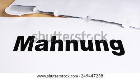 Mahnung german dunning or reminder letter with opened envelope on desk - stock photo