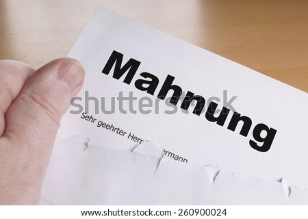 Mahnung male hand holding german dunning or reminder letter - stock photo