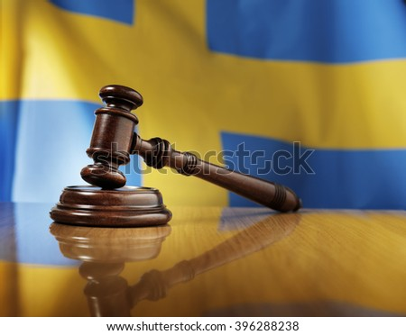 Mahogany wooden gavel on glossy wooden table, flag of Sweden in the background.