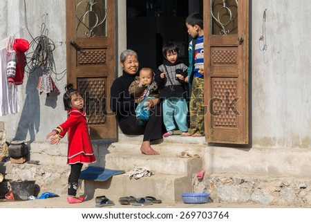 MAI CHAU, VIETNAM, DECEMBER 12, 2014: A happy Chinese grandmother and her grandchildren are enjoying the sunlight at the home entrance in the village of Mai Chau, Vietnam - stock photo