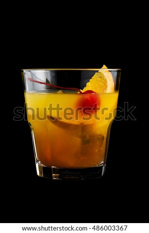 Mai Tai cocktail with orange and maraschino cherry garnish on black background