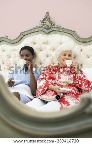 Maid and Employer Drinking Tea on Bed - stock photo