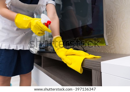 Maid cleaning a television cabinet spraying it with detergent before wiping it with a cloth, close up on her gloved hands