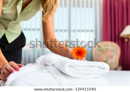 Maid doing room service in hotel, she is making up the beds - stock photo