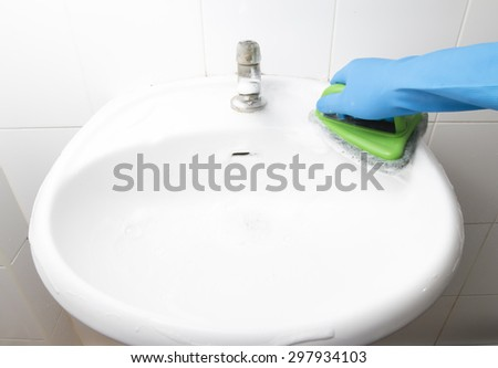 Maid in Blue Rubber Glove Cleaning White Washbasin