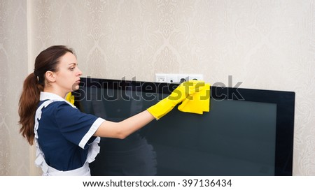 Maid or housekeeper cleaning a television set dusting the top with a yellow duster dressed in a neat uniform, profile upper body view - stock photo