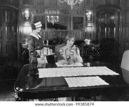 Maid serving woman at table - stock photo