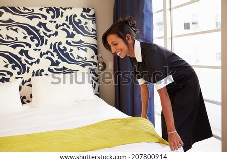 Maid Tidying Hotel Room And Making Bed - stock photo