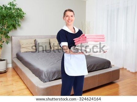 Maid woman with towels. House cleaning service concept. - stock photo