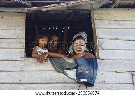 MAIGA ISLAND, MALAYSIA - JUNE 5 : Family of Sea Gypsy (Bajau Laut) at the window of wooden hut on June 5th, 2014 in Maiga Island, Sabah, Malaysia. - stock photo