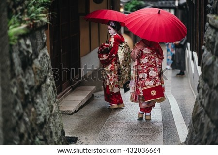 Maiko geisha walking on a street of Gion in Kyoto Japan - stock photo