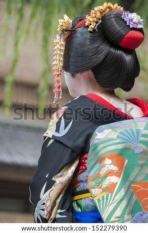 Maiko in the Gion section of Kyoto, Japan. This perspective shows the complex hair arrangement and white painted back that complements the colorful kimono.  - stock photo