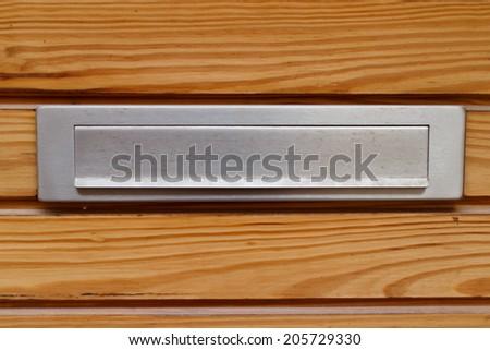Mail slot in wood door - stock photo