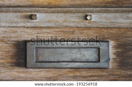 Mail slot letterbox in an old wooden door - stock photo