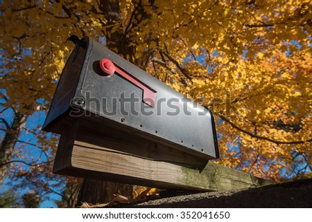 mailbox at the house along in yellow leaves during fall - stock photo